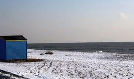 Beach Hut on a snow covered beach. A solitary beach hut on a snow covered beach in December Stock Photo