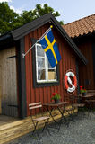 Beach Hut with Swedish Flag and Lifebuoy in Sweden Stock Images