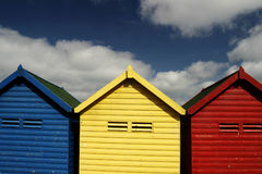 Beach Huts. Blue, red and yellow beach huts on the promenade at whitby seaside resort Royalty Free Stock Photos