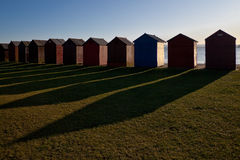 Beach Huts. A line of beach huts with strong sunlight casting long shadows across the ground in front Stock Image