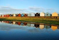 Beach huts. Landscape with very colorful beach huts reflected on the water. Picture is taken in late afternoon in Southwold, England Stock Image