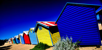 Colorful beach huts. Long row of intensely colorful beach huts on sandy Brighton beach, Melbourne, Australia Royalty Free Stock Image