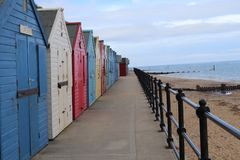 Beach huts all colours in a row , mundesley Norwich. Beach huts along the seashore .mundesley Norwich.colours of the rainbow stock photo