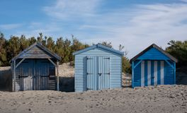 Beach huts behind the sand dunes on West Wittering beach, West Sussex UK. Photographed on a clear autumn morning.