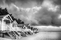 Beach huts in black and white on sandy coast. Elevated beach huts in Norfolk are some of the most beautiful in England, situated on the sandy North Norfolk coast Stock Photography