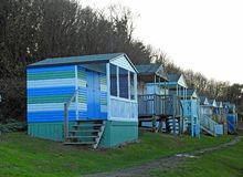 Beach huts chalets sheds in a row by the coast royalty free stock image
