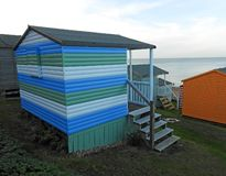 Beach huts chalets sheds in a row by the coast stock photography
