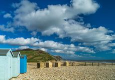 Beach huts and cloud formation at Charmouth,  Dorset. Beach huts and dramatic cloud formation at Charmouth, Dorset with shingle beach and barrier in foreground Stock Images