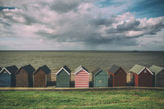 Beach huts on coast on cloudy rainy day in Kent, England. Cute beach huts in Kent, England Stock Images