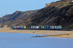 Beach huts at Cromer, Norfolk, england. Colourful beach huts below the cliffs, close to the beach at Cromer Norfolk England. Two figures are walking along the Stock Images