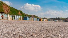 Beach Huts in Devon. Beach huts and the pebble beach in Budleigh Salterton, Jurassic Coast, Devon, UK royalty free stock photography