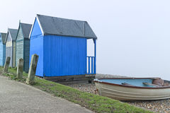 Beach huts and fishing boat on English seaside on a foggy day Stock Images