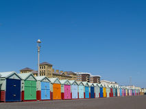 Beach huts lined up below clear blue sky. Stock Image
