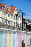 Beach Huts, Lyme Regis. Row of colourful beach huts along the edge of the beach and promenade with tourists enjoying the setting, Lyme Regis, Dorset, England Royalty Free Stock Photography