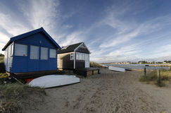 Beach Huts at Mudeford Spit. Beach huts and boats in sand dunes at Mudeford Spit on Hengistbury Head near Christchurch in Dorset Royalty Free Stock Photos