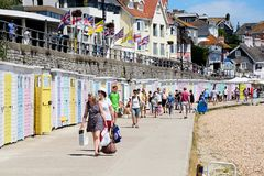 Beach huts and promenade, Lyme Regis. Row of colourful beach huts along the edge of the beach and promenade with tourists enjoying the setting, Lyme Regis Royalty Free Stock Image