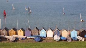 Beach huts and sailing yachts stock video