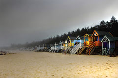 Beach Huts & Sea Mist - Norfolk UK. Sea-mist sweeps up a Norfolk beach & engulfs a long line of colourful beach huts Stock Photo