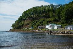 Beach huts on the sea shore under the green hill. Stock Photography