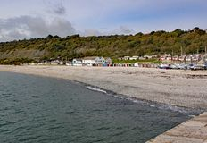 Beach huts on the shingle beach viewed from the Cobb at Lyme Regis, Dorset, England royalty free stock images