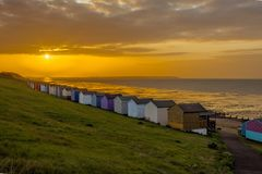 Beach huts. Sun setting behind beach huts on the south coast of england stock image