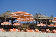 Beach huts and umbrellas Stock Photos