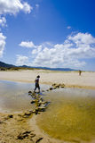 Beach II. Woman stepping over stones in water Stock Image