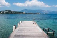 Beach of Ionian Sea, Corfu island. Wooden pontoon stretching into the sea in Greece, Corfu Royalty Free Stock Image