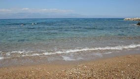The beach on Ionian Sea at luxury hotel and swimming tourists stock video footage