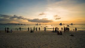 Beach on the island of Boracay in the rays of the evening sunset. Silhouettes of people playing a ball on the beach and. Sailboats on the water Stock Image