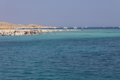 Beach island full of tourists + clear blue sea Stock Images