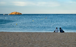 Beach and Islet in Tossa de Mar. Two girls with their backs on the beach stock photography