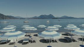 Beach Italy Como Maggiore lake holidays summer vacations drone flight umbrella. 4k blue water stock video