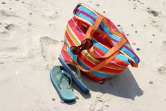 Beach items. Flip-flop, beach bag and sunglasses lying on the sand royalty free stock photos
