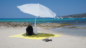 Beach items. An ideal beach spot with the typical beach items: towel, sandals, sun umbrella... in Formentera, Balearic islands (Spain Royalty Free Stock Photography