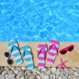 Beach items by the poolside. Flip flops, glasses and starfish by the poolside Stock Photos