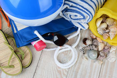 Beach Items Still Life. A group of items for a day at the beach, sandals, beach ball, tote bag, sunglasses, towel and sand pail with sea shells, and sun tan royalty free stock photos
