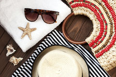 Beach items with straw hat,towel and sunglasses  on wooden background Royalty Free Stock Images