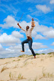 Beach jumping man. An African American male violinist with happy smiling facial expression in his black face jumping on a sand dune in front of blue sky Royalty Free Stock Photo