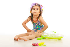 Beach kid girl with toys. Beach kid girl sitting with toys around and looking at camera royalty free stock image
