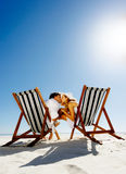 Beach kiss couple. Summer beach kissing couple sitting on deck chairs enjoying an intimate moment stock photography