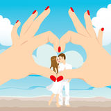 Beach Kiss Love Heart. Looking a couple kissing on the beach through love heart hand sign frame Stock Photos