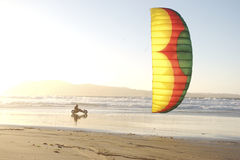 Beach Kite Buggying. A man kite buggying at the beach at sunset Stock Photo