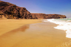 Beach La Pared on Fuerteventura, Spain. Beautiful beach La Pared with mixed golden and dark sand, ocean waves and rocks on the Canary Island Fuerteventura Stock Images