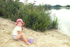 The beach at the lake in the sand a little girl in a hat playin Royalty Free Stock Photography