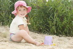 The beach at the lake in the sand a little girl in a hat playin Stock Photography