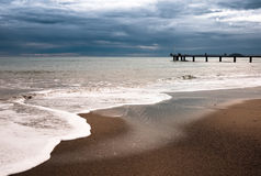 Beach landscape. With a modern pier in the background Stock Images