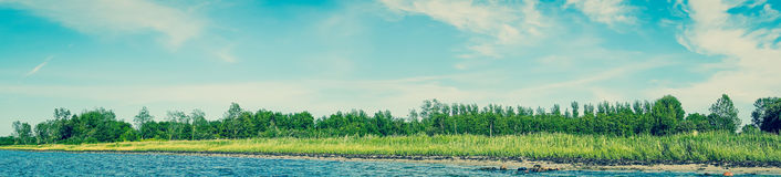 Beach landscape with blue water and green trees. Panorama landscape of a Scandinavian beach with green trees and blue water Stock Photo