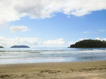 Sunny beach landscape in Brazil, with island in the background. Beach landscape in Brazil, with waves, sand, island in the background and sky with clouds Stock Photo