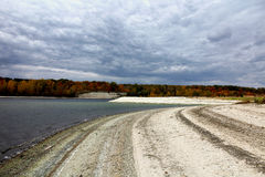 Beach landscape covered with light colored pebbles under gray cloudy sky. And autumn forest Royalty Free Stock Photos